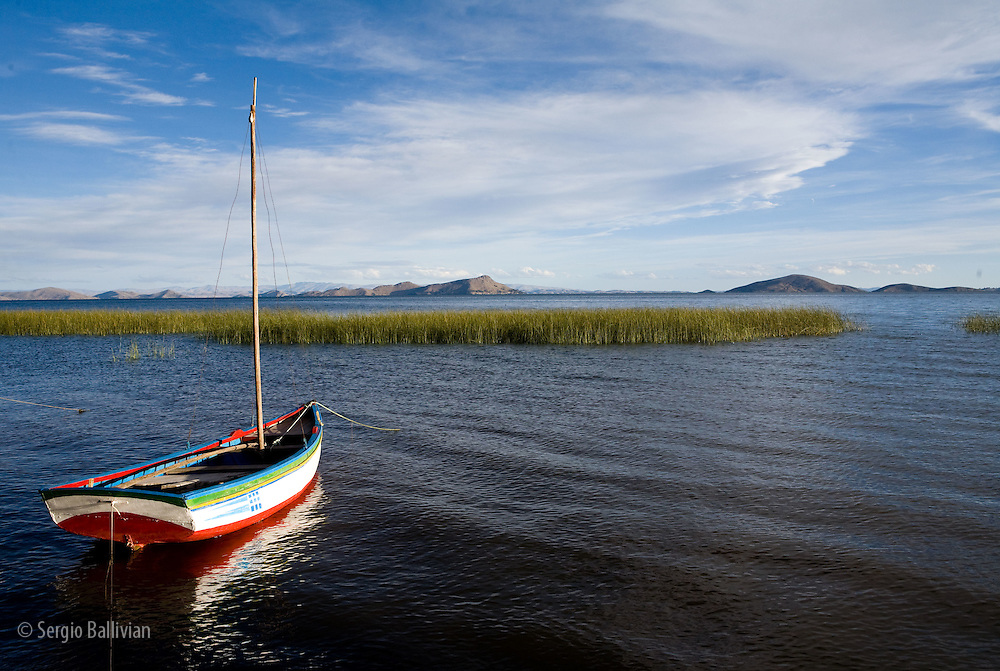 A typical wooden fishing boat on Lake Titicaca in Bolivia sits anchored at sunset protected by Totora Reed beds.