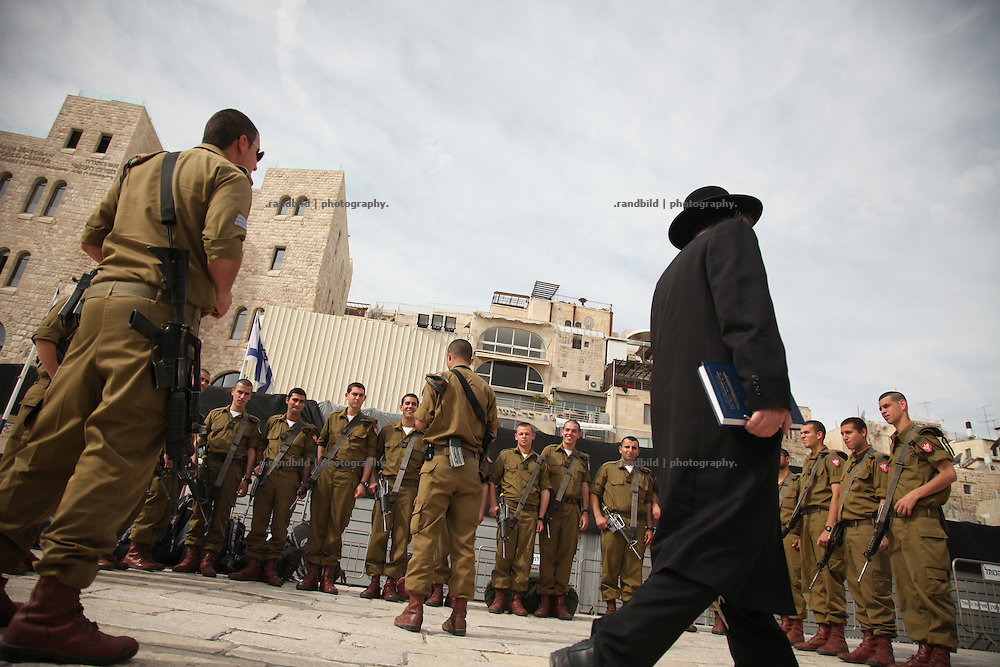 Worshippers at the Wailing Wall (Western Wall) in Jerusalem in the morning. Beside a lot of orthodox jews, many IDF soldiers come to pray, carrying their assault rifle.