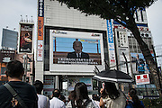 People watch a screen showing Japanese Emperor Akihito delivering a speech in Tokyo, Monday, Aug. 8, 2016. The Japanese emperor, in a rare address to the public, signaled Monday his apparent wish to abdicate by expressing concern about his ability to carry out his duties fully. 08/08/2016-Tokyo, JAPAN