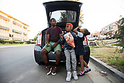 """After training with his speed coach Jonathan Ligons, 35, left, Maxwell """"Bunchie"""" Young, 10, did a quick change into clothes for bible study, and snacks on some potato chips with his sister Maxine, 4, while talking about football with Ligons."""
