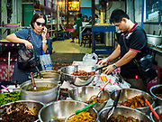 28 MAY 2018 - BANGKOK, THAILAND: A worker in a Burmese lunch stand prepares an order to go in Phra Khanong Market in Bangkok. The market serves a mix of Thai working class people and immigrants from Myanmar (Burma).     PHOTO BY JACK KURTZ