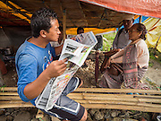 05 AUGUST 2015 - KATHMANDU, NEPAL: A man reads a newspaper in an informal tea shop in a large Internal Displaced Person (IDP) Camp in the center of Kathmandu. The camp is next to one the most expensive international hotels in Kathmandu. More than 7,100 people displaced by the Nepal earthquake in April live in 1,800 tents spread across the space of three football fields. There is no electricity in the camp. International NGOs provide water and dug latrines on the edge of the camp but the domestic waste water, from people doing laundry or dishes, runs between the tents. Most of the ground in the camp is muddy from the running water and frequent rain. Most of the camp's residents come from the mountains in northern Nepal, 8 - 12 hours from Kathmandu. The residents don't get rations or food assistance so every day many of them walk the streets of Kathmandu looking for day work.    PHOTO BY JACK KURTZ