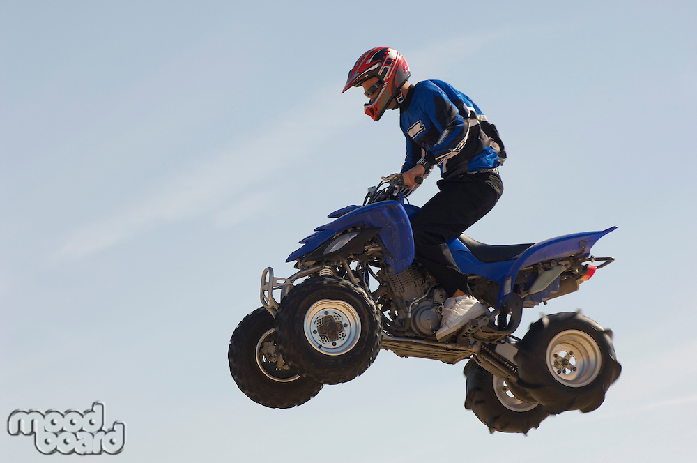 Man riding quad bike in mid-air against blue sky close up