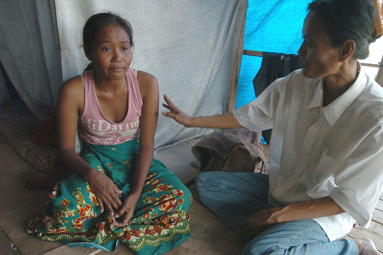 Cambodia. Phnom Penh. February, 2006. Hen, an outreach worker with Chhouk Sar; a small NGO run by HIV positive former and current sex workers, cares for an HIV positive pregnant sex worker, The young women is sick and is very poor living under a makeshift tent in a slum