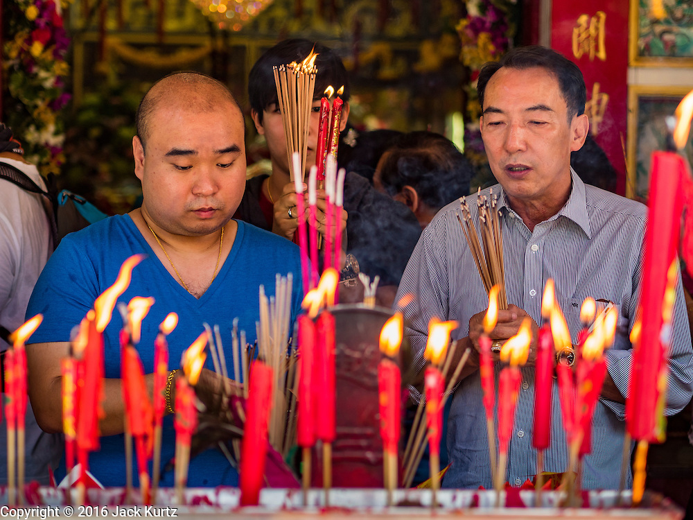 16 SEPTEMBER 2016 - BANGKOK, THAILAND: Men pray at Heng Chia Shrine on Chareon Krung Road during the Mid-Autumn Festival in Bangkok. The festival was originally a time to enjoy the successful reaping of rice and wheat and is still celebrated as a harvest festival in agricultural communities. In Bangkok, people make food offerings in honor of the moon. And it is an opportunity to share mooncakes.   PHOTO BY JACK KURTZ