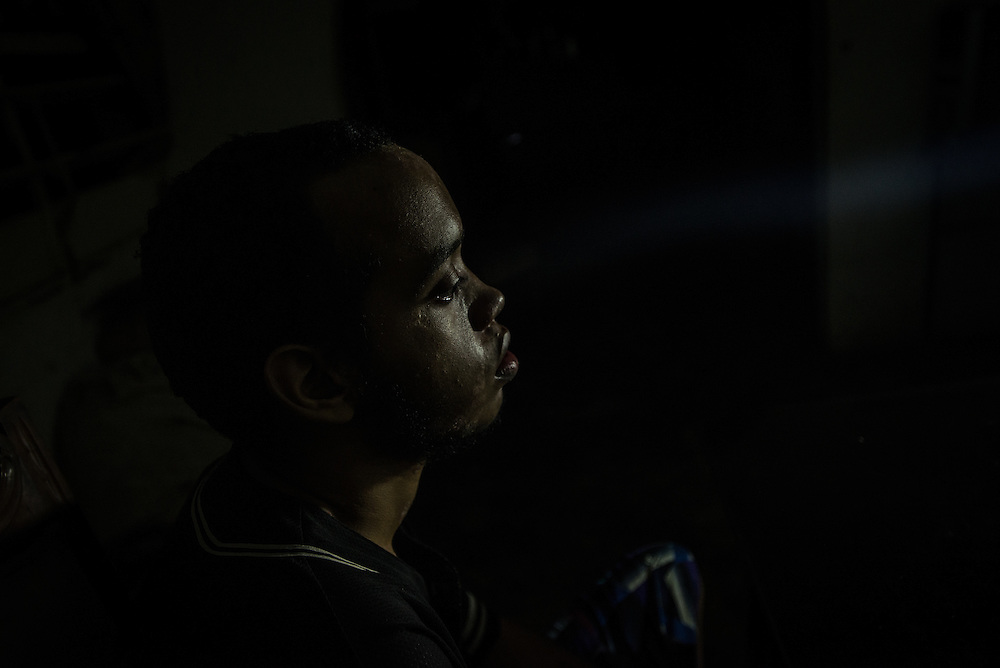 """MARACAY, VENEZUELA - JULY 15, 2016: Schizophrenic Gerardo Simeone sits at the dinner table during a power outage, which are frequent in this town. He spends most of his days either sleeping, or standing in a corner in silence in his family's living room, rarely even making eye contact with members of his family.  His parents remember how he used to be when he was younger…before he became ill - recalling how affectionate and talkative he was. """"He was so kind and loving,"""" said his mother, Evelin.  Gerardo's brother Accel is also schizophrenic. Their parents spend hours each week searching pharmacies for the psychiatric drugs that thier sons need, which are very difficult to find, because of nationwide shortages.  """"I am tired,"""" Evelin said. """"This is too much sometimes"""".  PHOTO: Meridith Kohut for The New York Times"""