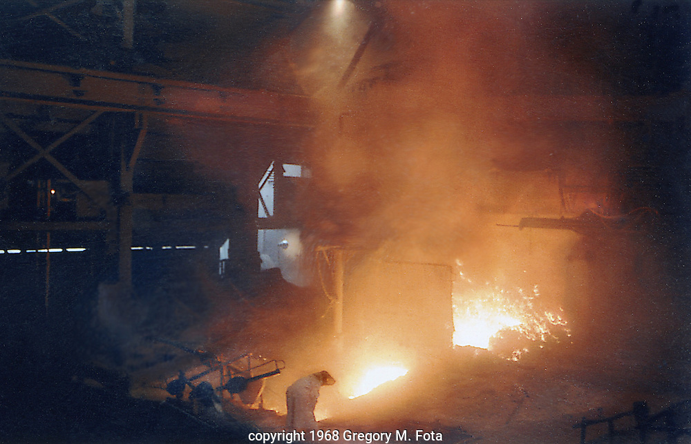 BLAST FURNACE TAP--A steelworker in protective clothing watches the path of molten iron and slag as it passes through sand-lined troughs on the floor of a blast furnace at Bethlehem Steel Co.,Bethlehem,PA, 1968. (copyright 1968 Gregory M. Fota)