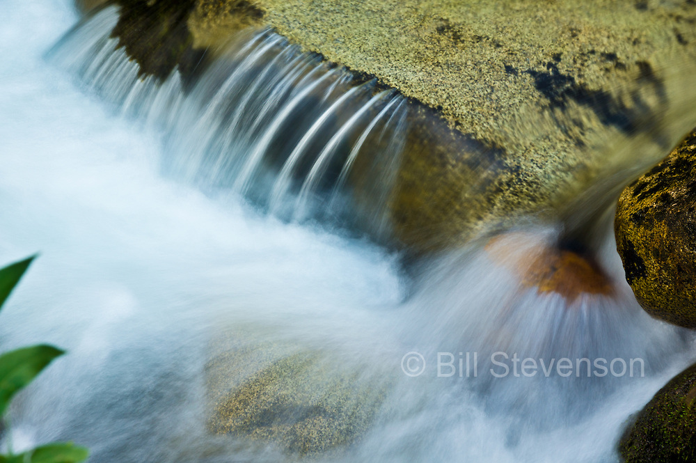 A photo of a stream running over granite rocks in McGee Creek in the sierras.