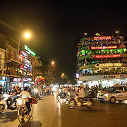 An intersection with busy traffic at night in Hanoi's Old Quarter, next to Hoan Kiem Lake.