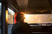 A lady passenger's red hair glows in backlit winter sunlight through the front window while travelling on a bus along Piccadilly, on 20th January 2020, in London, England.