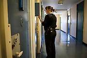 A female prison officer checks on a prisoner through the door window before entering the cell. Beaufort House, a skill development unit for enhanced prisoners. Part of HMP/YOI Portland, a resettlement prison with a capacity for 530 prisoners.Dorset, United Kingdom.