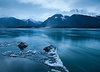 Blue light before the dawn over a freezing river in Haines, Alaska, USA. The wind is picking up and bringing in a sandstorm.