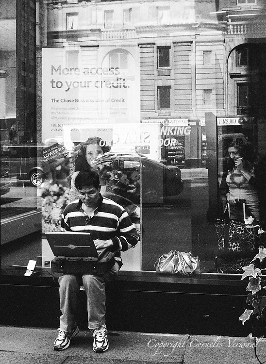 Man with laptop and satellite antenna communicates maybe with the reflected woman on the phone.<br /> Sixth Avenue and 56th Street, New York City.
