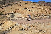 Person cycling in Cabo de Gata national park, Monsul, near San José, Almeria, Spain