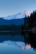 Mount Baker reflects in the rippled waters of Baker Lake at sunrise on a lightly breezy summer morning.