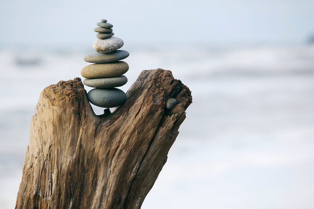 Stacked stones balancing on log.