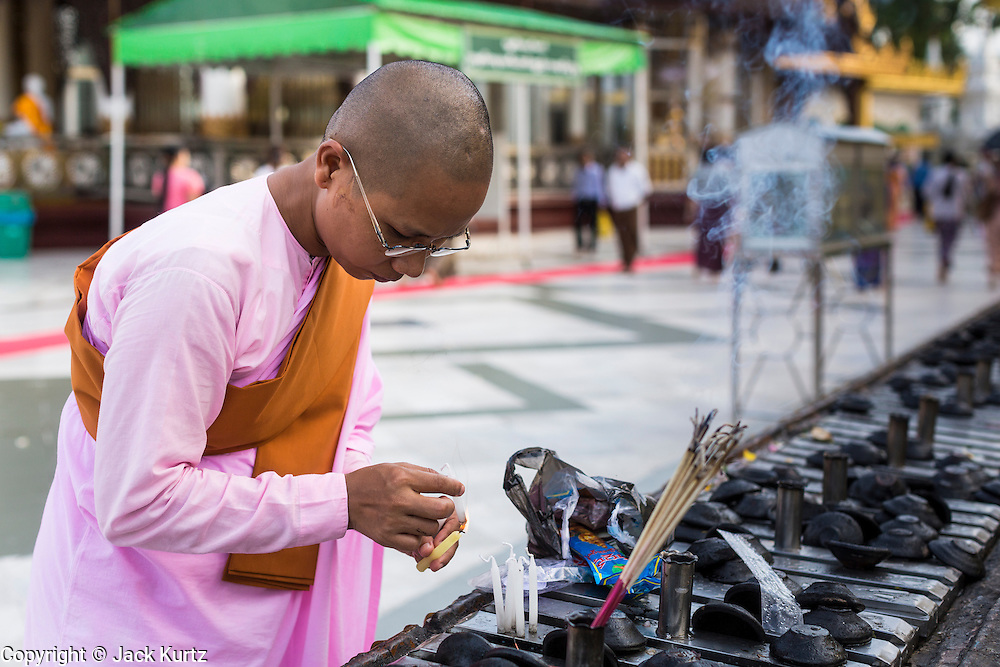 15 JUNE 2013 - YANGON, MYANMAR: A Buddhist nun lights candles while praying at Shwedagon Pagoda. Shwedagon Pagoda is officially known as Shwedagon Zedi Daw and is also called the Great Dagon Pagoda or the Golden Pagoda. It is a 99 meter (325 ft) tall pagoda and stupa located in Yangon, Burma. The pagoda lies to the west of on Singuttara Hill, and dominates the skyline of the city. It is the most sacred Buddhist pagoda in Myanmar and contains relics of the past four Buddhas enshrined: the staff of Kakusandha, the water filter of Koṇāgamana, a piece of the robe of Kassapa and eight strands of hair from Gautama, the historical Buddha. Burmese believe the pagoda was established as early ca 540BC, but archaeological suggests it was built between the 6th and 10th centuries. The pagoda has been renovated numerous times through the centuries. Millions of Burmese and tens of thousands of tourists visit the pagoda every year, which is the most visited site in Yangon. PHOTO BY JACK KURTZ