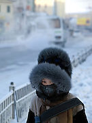 Schoolchild protected with a traditional fur cap and warm clothing against the extrem cold. Yakutsk is a city in the Russian Far East, located about 4 degrees (450 km) below the Arctic Circle. It is the capital of the Sakha (Yakutia) Republic (formerly the Yakut Autonomous Soviet Socialist Republic), Russia and a major port on the Lena River. Yakutsk is one of the coldest cities on earth, with winter temperatures averaging -40.9 degrees Celsius.