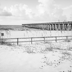 Pensacola Gulf Pier and wooden beach fence black and white photo. Pensacola Beach is a coastal city along the Gulf of Mexico in the Southeastern United States. Photo is high resolution. Copyright ⓒ 2018 Paul Velgos with All Rights Reserved.