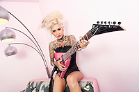 Portrait of a tattooed woman wearing corset while holding guitar against wall