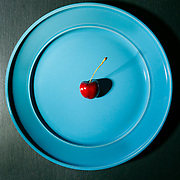 Single cherry on a blue plate, in studio, dark food photography