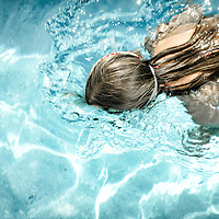 Female youth swimming in pool with face in water