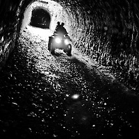 Quad bike in a tunnel at Clapham in the Yorkshire Dales.  Backlit or contre jour daylight.