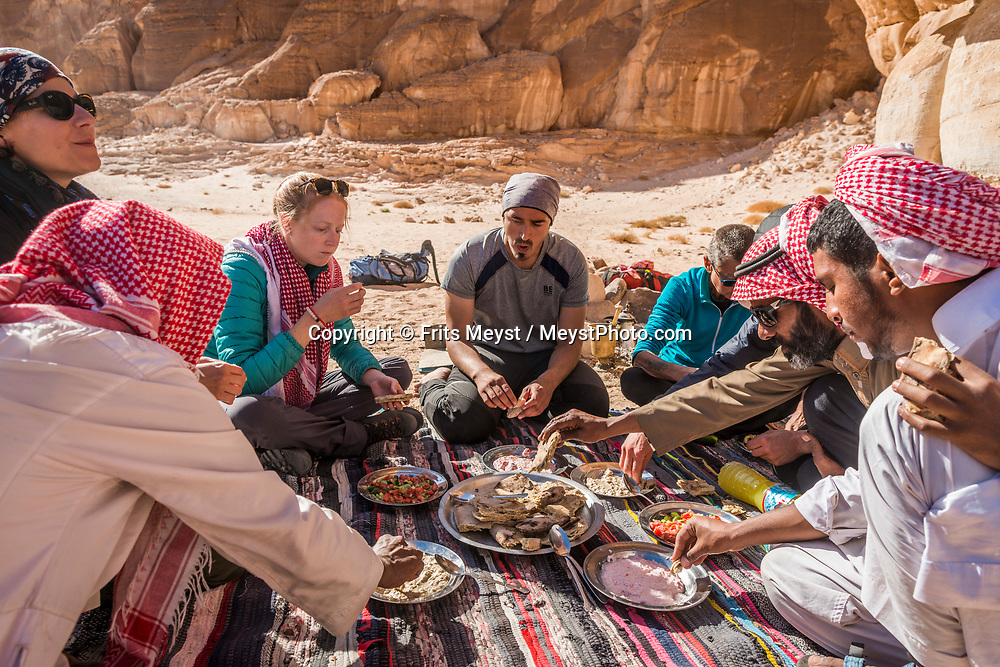 Sinai, Egypt, December 2018. Lunch with Bedouin bread made on hot ash in Wadi Hudera while hiking with the Tarabin Tribe through the Sinai Desert Coastal Ranges. The Sinai Trail is Egypt's 1st long distance hiking trail, running 230km from the Gulf of Aqaba to the top of the Sinai's highest mountain. It connects old trade, travel and pilgrimage routes through one of the Middle East's most iconic desert wildernesses and is managed by a cooperative of three Bedouin tribes. Photo by Frits Meyst / MeystPhoto.com