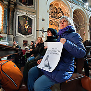 VENICE, ITALY - JANUARY 15:  A woman holds a sign asking to protect the pigeons while she attends a special service with a blessiing of  pets and animals held by Don Filippo Chiafoni Chaplain of the Church of S Francesco da Paola on January 15, 2012 in Venice, Italy. The blessing of animals and pets is a very ancient tradition dating back from San Francis of Assisi.
