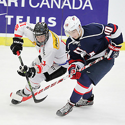COBOURG, - Dec 16, 2015 -  Game #7 - United States vs Switzerland at the 2015 World Junior A Challenge at the Cobourg Community Centre, ON. Dominik Volejnicek #11 of Team Switzerland battles for the puck with Tanner Laczynski #10 of Team United States during the first period.(Photo: Tim Bates / OJHL Images)