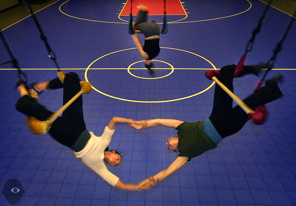 (Front LtoR) Pendulum members Shanti Markstrom and Pamela Clark twist while linked at the arms as Emily Scherb (rear center) flips about the bar during their areial dance company rehearsal.