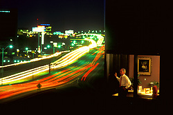 Stock photo of a businessman in a corner office overlooking passing freeway traffic at night
