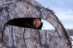 Wildlife photojournalist Noppadol Paothong at work in a blind in south-central Wyoming. ©John L. Dengler / DenglerImages.com