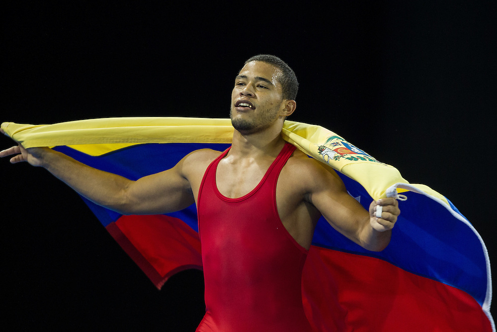 Gold medalist Wuileixis Rivas of Venezuela runs with his flag following his win over Bryce Saddoris of the United States in the 66kg class of the men's greco-roman wrestling at the 2015 Pan American Games in Toronto, Canada, July 15,  2015.  AFP PHOTO/GEOFF ROBINS