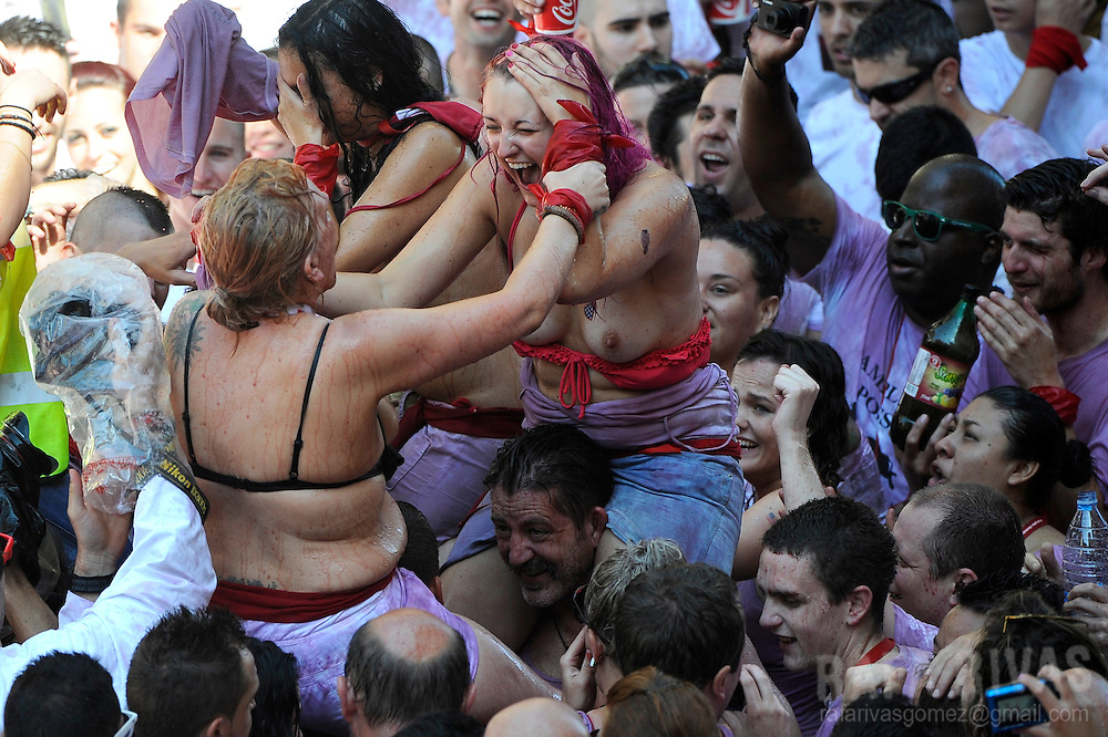 Participants celebrate during the 'Chupinazo' to mark the start of the San Fermin Festival on July 6, 2013 in front of the Town Hall of Pamplona, northern Spain. Tens of thousands of people packed Pamplona's streets for a drunken kick-off to Spain's best-known fiesta: the nine-day San Fermin bull-running festival.