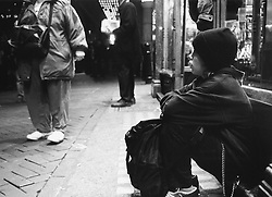 Young homeless runaway boy sitting on street pavement with bag,
