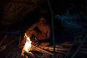 A Maniq man sits in his small hut warming himself by the fire.<br /> <br /> Evidence suggests that the Maniq, a Negrito tribe of hunters and gatherers, have inhabited the Malay Peninsula for around 25,000 years. Today a population of approximately 350 maniq remain, marooned on a forest covered mountain range in Southern Thailand. Whilst some have left their traditional life forming small villages, the majority still live the way they have for millennia, moving around the forest following food sources. <br /> <br /> Quiet and reclusive they are little known even in Thailand itself but due to rapid deforestation they are finding it harder to survive on the forest alone and are slowly being forced to move to its peripheries closer to Thai communities.