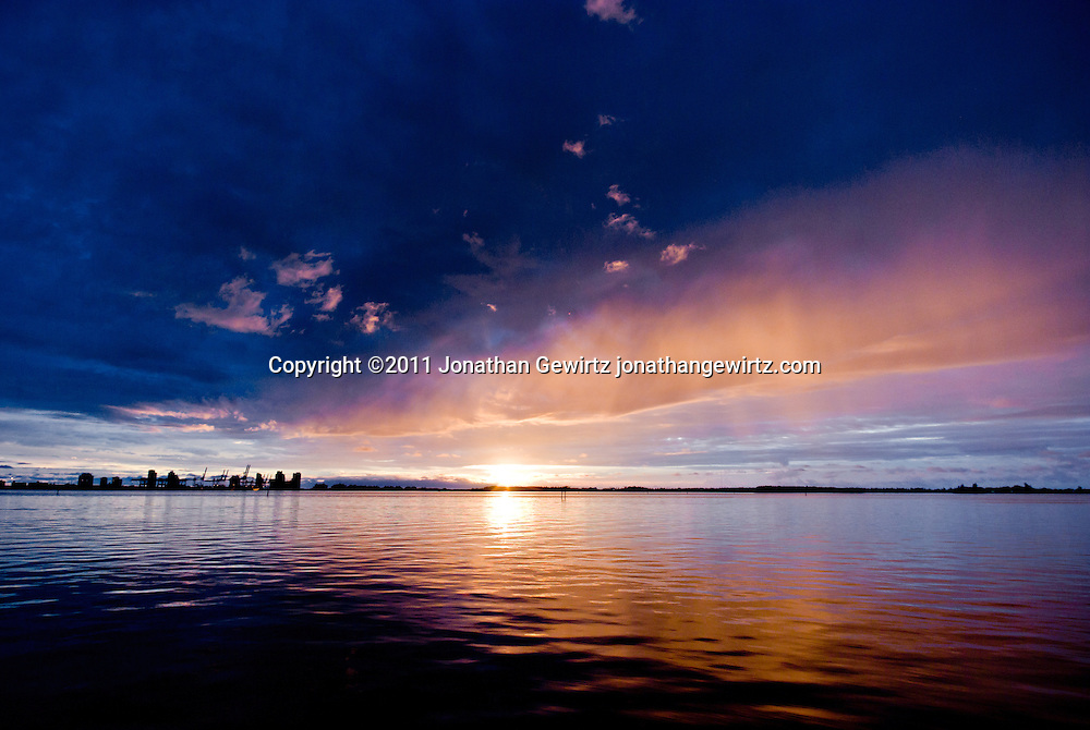 An advancing rain shower is backlit by the rising sun on Biscayne Bay with the Port of Miami in the left background and the northern end of Virginia Key in the right background. WATERMARKS WILL NOT APPEAR ON PRINTS OR LICENSED IMAGES.