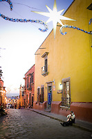 A man with a guitar, mariachi, plays on the cobblestone street in San Miguel de Allende on Christmas Eve.