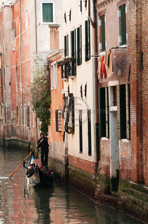 Gondolier provides boat tour of Venice to tourists (Italy).