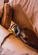 A hiker squeezes out of the narrow east fork (down from the Inscription Chamber) of Leprechaun Canyon in North Wash, between Hanksville & Hite, Utah, USA. Leprechaun Canyon's sandstone dates from the Triassic-Jurassic Period. Directions: from Hanksville, drive 26 miles south on Highway 95 to the junction with Utah 276 and stay left on H95 for another 2.0 miles across a wash, then park on the left (east) along a short road within the first 100 feet before its sandtrap end. Walk up the wash of Leprechaun Canyon 2 miles round trip to a gorgeous subway which narrows to a tight squeeze called Belfast Boulevard. Nearby, Glen Canyon National Recreation Area is just 8 miles south on H95.