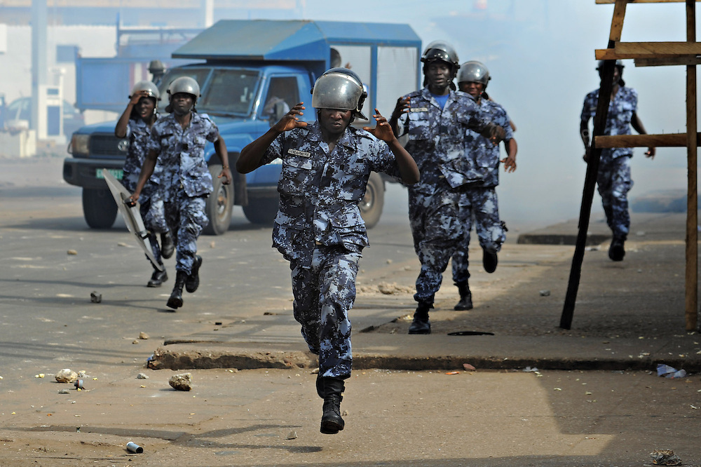 LOME, TOGO - 12-10-05   - Gendarmes rush a group of protesters during clashes in Lomé on October 5. A peaceful protest was scheduled by opposition groups, but their route was blocked by police.  For months, opposition parties have been calling for the departure of president Faure Gnassingbe, whose family has been in power for over 40 years.   Photo by Daniel Hayduk