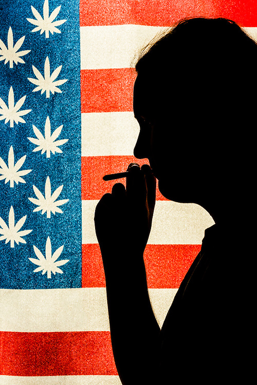 Man smoking a joint with American marijuana flag in background, Littleton, Colorado USA.  Colorado was the first state to legalize the sale of marijuana for recreational use in 2014.