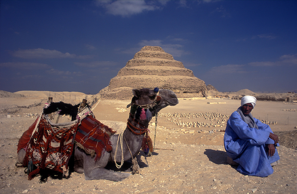 A camel herder and his camel relax in front of the ancient Step Pyramid of Zoser at Saccara.