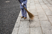 A woman sweeps pepples off the walkways at the Fuji Inari shrine in Kyoto, Japan.