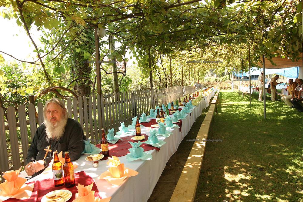 Georgien/Abchasien, Gudauta, 2006-08-26, Ein orthodoxer Priester als Ehrengast vor Beginn des Festes. Auf dem traditionellen Treffen des Hagba-Clans in Abchasien kommen 125 Familien zusammen. Vor dem Fest diskutieren die Männer die Probleme und sammeln Geld für notleidende Familienmitglieder. Abchasien erklärte sich 1992 unabhängig von Georgien. Nach einem einjährigen blutigen Krieg zwischen den Abchasen und Georgiern besteht seit 1994 ein brüchiger Waffenstillstand, der von einer UNO-Beobachtermission unter personeller Beteiligung Deutschlands überwacht wird. Trotzdem gibt es, vor allem im Kodorital immer wieder bewaffnete Auseinandersetzungen zwischen den Armee der Länder sowie irregulären Kämpfern. (A meeting of the Hagba clan in Abkhazia. 125 families depends on that clan. At the traditional meeting every summer the men discuss the problems and collecting money for needy family members. After that the party begins. Abkhazia declared itself independent from Georgia in 1992. After a bloody civil war a UNO mission observing the ceasefire line between Georgia and Abkhazia since 1994. Nevertheless nearly every day armed incidents take place in the Kodori gorge between the both armys and unregular fighters )