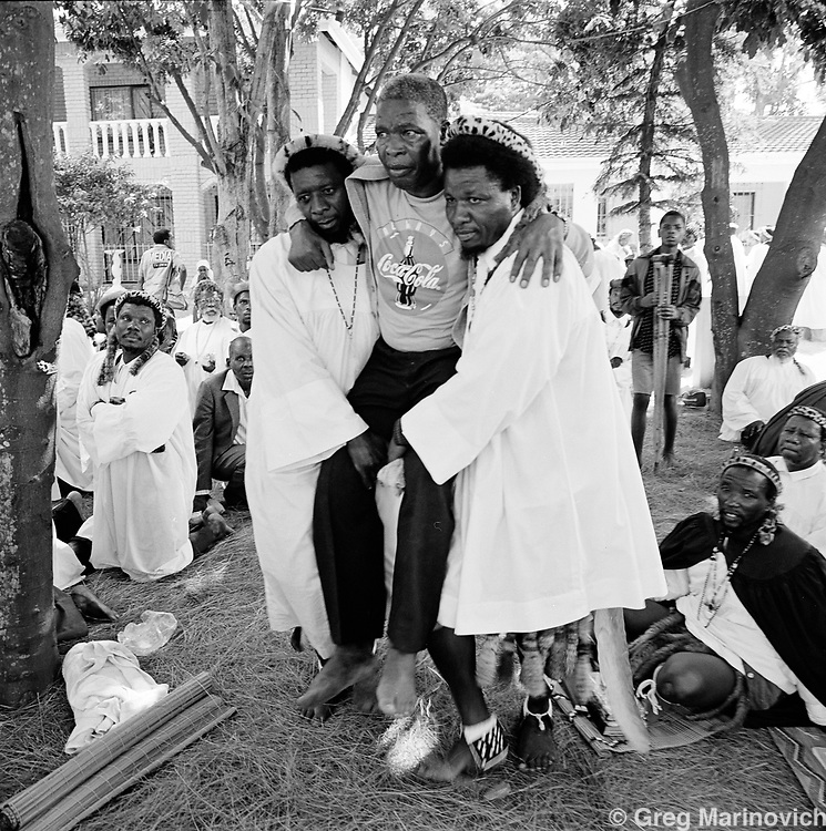Ekuphakameni, KwaZulu Natal. An ill man is brought to the headquarters of the Nazareth Baptist Church, or Shembe, hoping for a miracle. Shembe is a staunchly traditionalist Zulu cult that was founded in 1913 by Isiah Shembe after a vision. Their beliefs are a mix of Old and New Testament and the ancestral veneration of traditional Zulu culture.