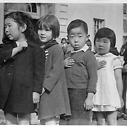 Many children of Japanese ancestry attended Raphael Weill public school, Geary and Buchanan Streets, prior to evacuation. This scene shows first-graders during flag pledge ceremony. Evacuees will be housed for the duration in War Relocation Authority centers. Provision will be effected for continuance of education. -- Photographer: Lange, Dorothea -- San Francisco, California. 4/20/42<br /> Identifier:<br /> Volume 57<br /> Identifier:<br /> Section G<br /> Identifier:<br /> WRA no. A-548<br /> Collection:<br /> War Relocation Authority Photographs of Japanese-American Evacuation and Resettlement Series 14: Preevacuation<br /> Contributing Institution:<br /> The Bancroft Library. University of California, Berkeley.