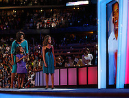 Michelle Obama (L), wife of presumptive Democratic presidential nominee Sen. Barack Obama (D-IL), and their daughters Malia (R), 10, and Sasha, 7, talk with their father via live satellite at the 2008 Democratic National Convention at the Pepsi Center in Denver, Colorado on August 25, 2008. (UPI)