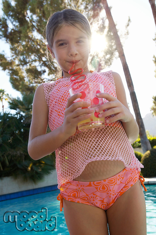Girl drinking juice from crazy straws by swimming pool, portrait